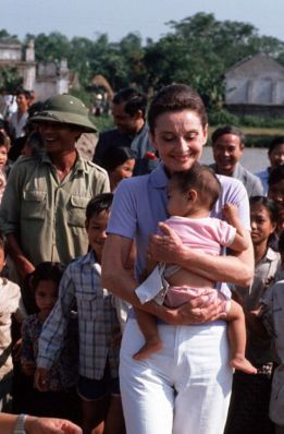 HANOI, VIETNAM - 1990/10/01: Audrey Hepburn, UNICEF's Goodwill Ambassador, clutches a small Vietnamese baby to her chest as she takes a walk about while visiting a small village close to Hanoi.. (Photo by Peter Charlesworth/LightRocket via Getty Images)
